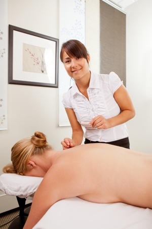 Portrait of a happy acupuncturist in her clinic with a female patient Stock Photo - 10700468