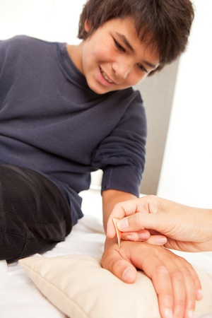 Young male receiving shonishin acupuncture on his hand with a Yoneyama tool.  Shallow depth of field, focus on tool. photo
