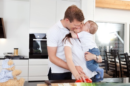 human relations: Happy family preparing a meal and getting a big hug