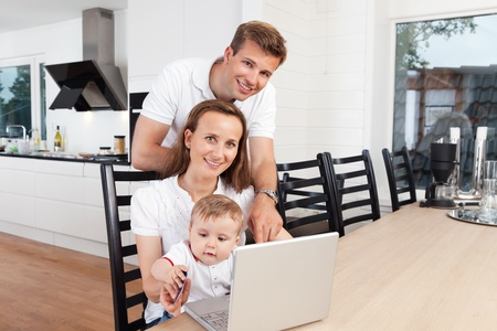 holding family together: Family of three smiling with laptop at table