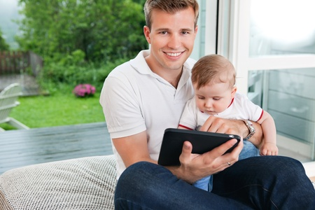 Portrait of smiling man using digital tablet while sitting with child photo