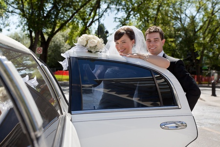 Happy wedding couple getting in car and looking at camera photo