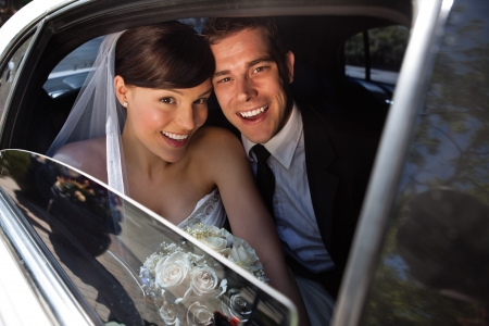 Portrait of happy newly wed couple in car photo