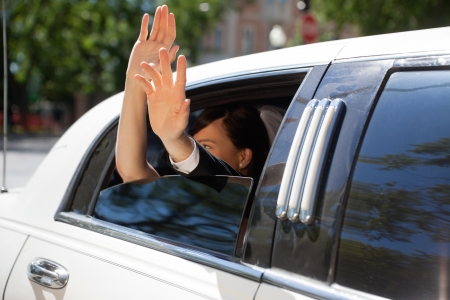 leaving: Happy newlywed couple waving out of limousine window