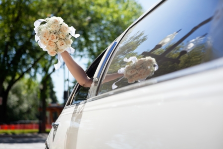 Bride waving hand from car holding flower bouquet photo