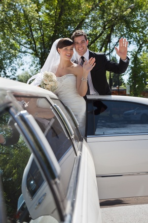Bride and groom standing in Limo waving photo