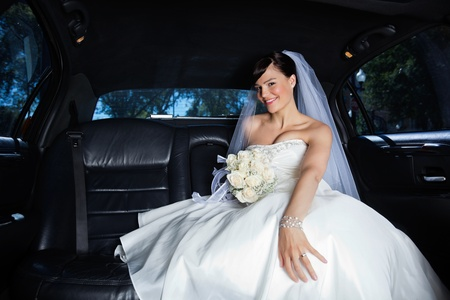 Beautiful bride sitting in car holding flower bouquet photo