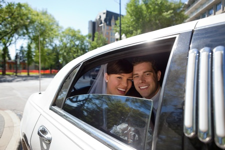 Portrait of newlywed couple in limousine photo