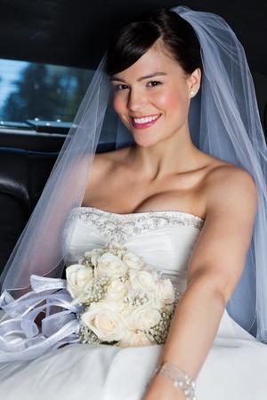Portrait of happy beautiful bride in limousine photo
