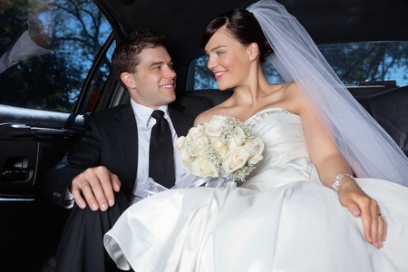 Happy newlywed couple in a luxurious car photo