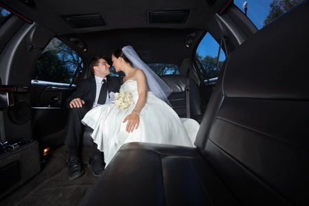 Loving newlywed bride and bridegroom in car photo