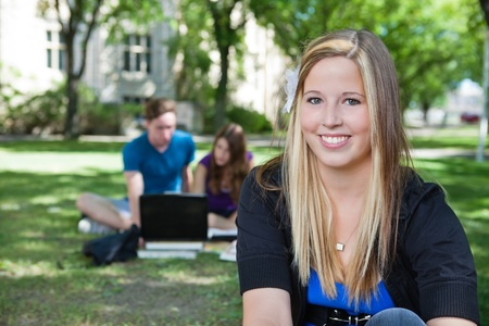 Portrait of happy teenage girl with classmates in background photo