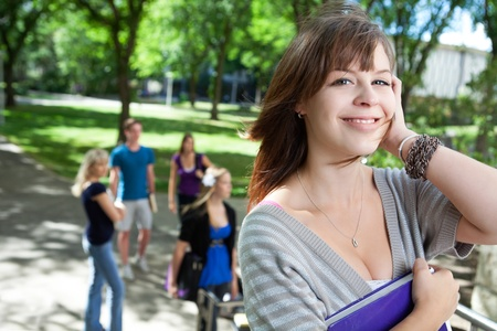 Portrait of young college girl smiling with friends in background photo