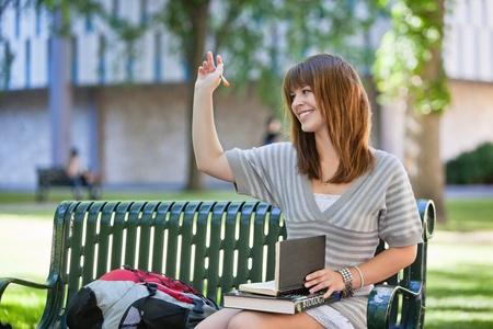 saluta: Giovane studentessa sorridendo agitando la mano di persona al di fuori dell'immagine Archivio Fotografico
