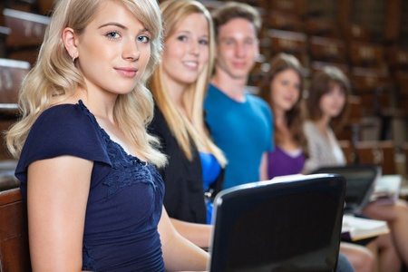 Group of students sitting in a row with laptop and book at seminar hall photo
