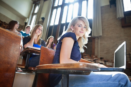 Portrait of college girl using laptop while students sitting in background photo