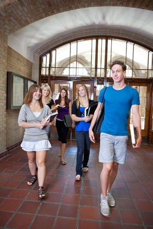Group of college students walking through hall photo