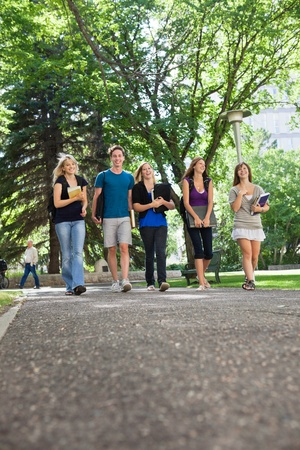 Group of happy young students walking to college photo