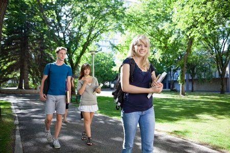 Group of students on their way to class walking through campus photo