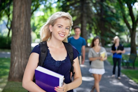 Portrait of happy young girl smiling while her classmates walking in background photo