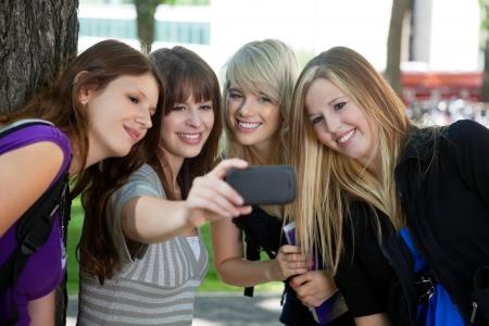 group picture: Adolescente que toma un autorretrato de sus amigas Foto de archivo