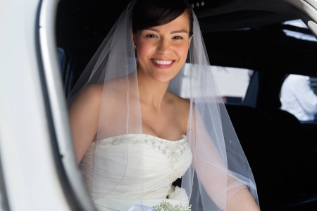 Attractive bride sitting in car and smiling photo