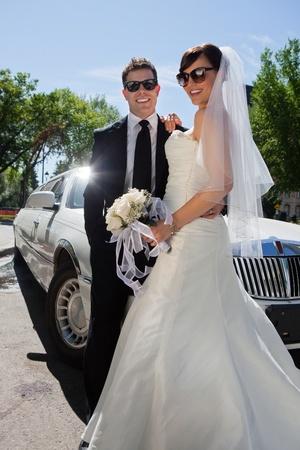 to wed: Due sposi in occhiali da sole in piedi vicino limousine