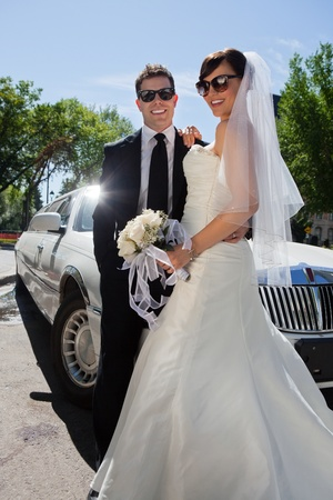 Newly wed couple in sunglasses standing near limousine photo