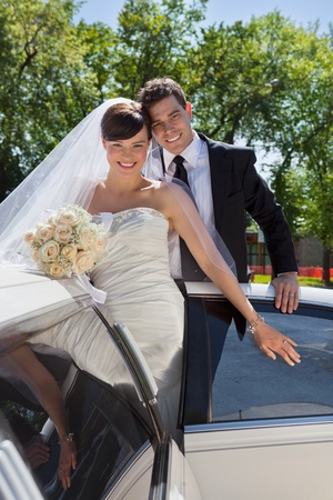 Happy newly wed couple getting in the car Stock Photo - 10762506