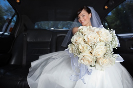 Attractive bride showing off her flower bouquet photo