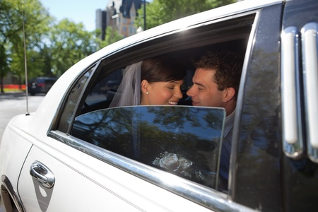 Newly wed romantic couple in car photo