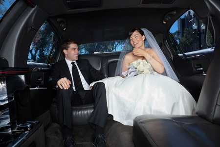 Bride and bridegroom in a luxury wedding limousine photo