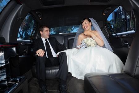 wedding suit: Bride and bridegroom in a luxury wedding limousine
