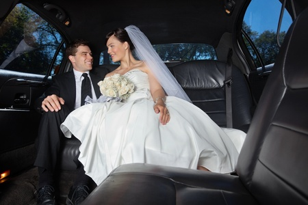 Newlywed bride and bridegroom in car photo
