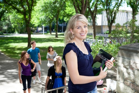 freshmen: Portrait of sweet young girl going to college with friends in background