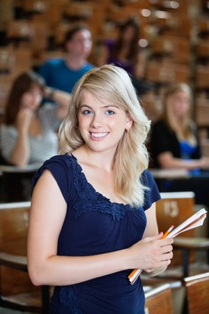 Portrait of young girl standing in auditorium with classmates in background photo