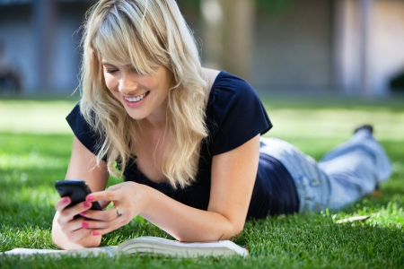 smart girl: Smiling young college girl texting on a cell phone Stock Photo