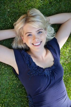 beautiful blonde girl with green eyes: Portrait of happy young woman lying on grass