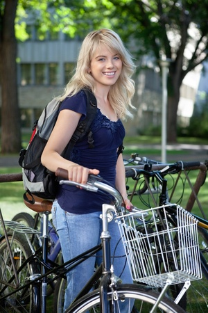 Portrait of attractive blonde female student standing with her bike photo