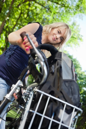 teenage girl happy: Low angle view of cute female student standing with her bike