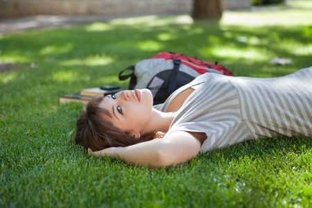 Young college student lying on grass at campus lawn photo