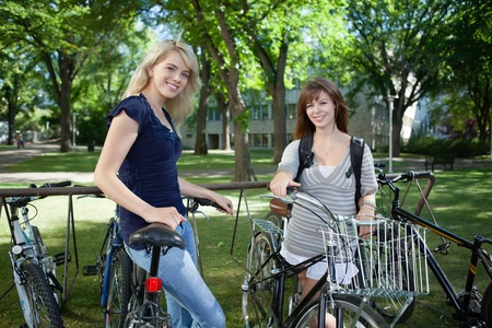 Young female students standing with bicycle at college campus lawn photo