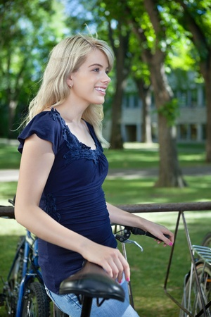 Thoughtful female student standing with her bike at college campus photo
