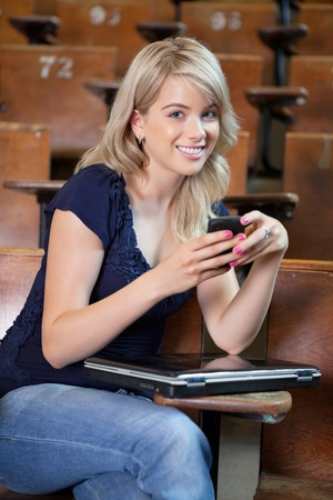 Portrait of young college girl using cell phone photo