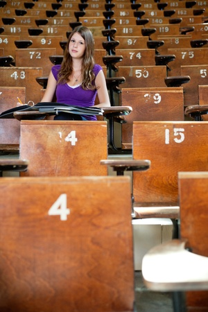 Young student sitting in empty lecture hall photo