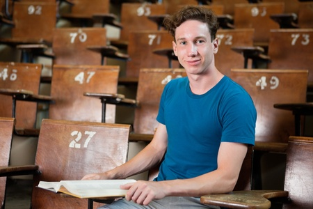 Portrait of young university student sitting in lecture hall photo