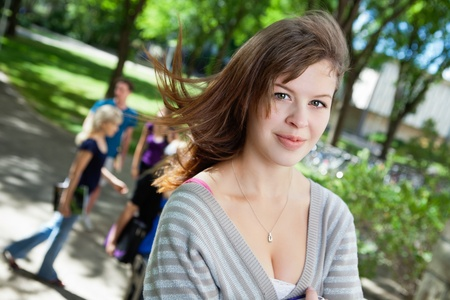 freshmen: Portrait of a sweet college girl with friends in background Stock Photo