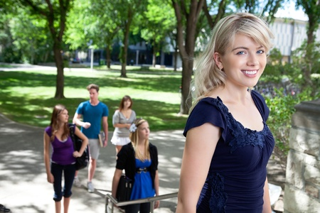 freshmen: Portrait of college girl going college with friends in background