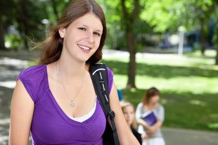 freshmen: Portrait of a sweet college girl smiling with friends in background