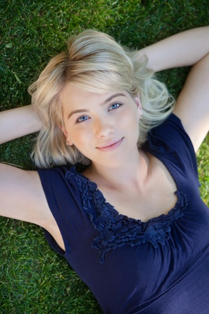 lay down: Portrait of young woman lying on grass